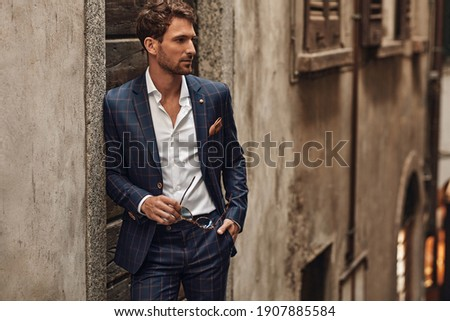 Handsome man in classik checked suit thinking Royalty-Free Stock Photo #1907885584