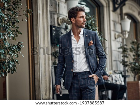Handsome male model in checked suit walking on the street Royalty-Free Stock Photo #1907885587