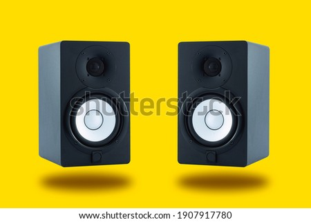 Pair of professional high quality monitor speakers for sound recording, mixing, and mastering in studio in black wooden casing isolated on yellow background. Front or Side view.