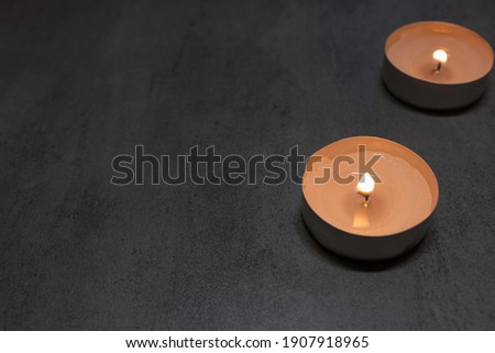 Two big burning candles. Bright light on dark background. RIP darkness template. Birthday party. Romantic evening on Valentine.