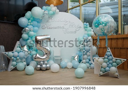 Arch of blue balloons for boy happy birthday party. Number 5 and 1 for two brothers. Festive decorative elements, photo zone with star. Inscription Nikita, Sasha. Royalty-Free Stock Photo #1907996848