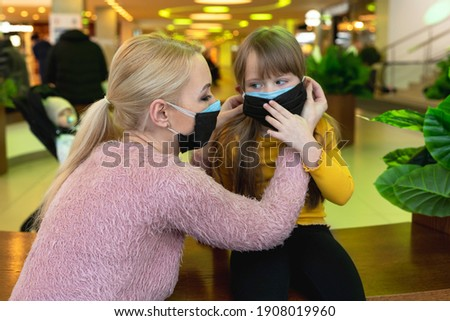 new trend, double mask. a woman in two masks, dresses her nofocused daughter a second mask Royalty-Free Stock Photo #1908019960