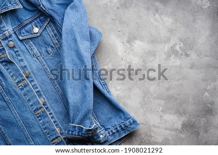 Classic jeans texture. Blue denim jacket on a gray background, space for text. Top view.  Royalty-Free Stock Photo #1908021292