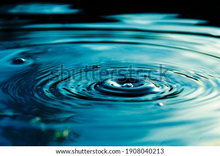 Circular waves and ripples in the water from a drop falling. Natural background blue water with circles and sky reflection. Royalty-Free Stock Photo #1908040213