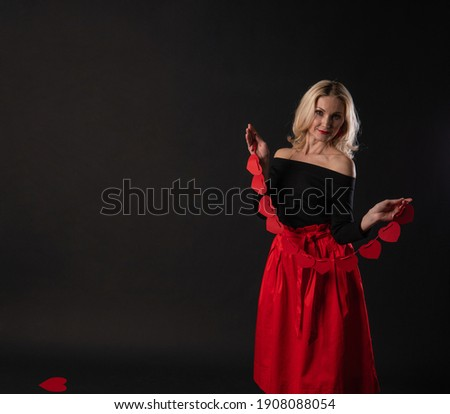 Girl holding a garland heart love symbol, flirting, on the floor hearts romance space. form a banner. emotion forever, engagement in the red dress girl, barefoot
