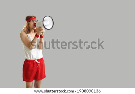 Funny noisy crazy nerdy man in sports shorts yelling in megaphone, announcing important marketing message, advertising workout wear and gym equipment sale, standing on grey empty space background