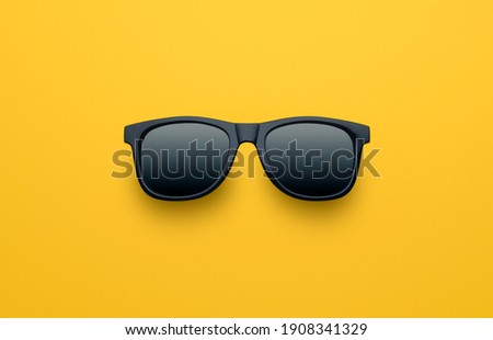 Black sunglasses on yellow background, top view, flat lay, minimalistic concept of summer, vacation Royalty-Free Stock Photo #1908341329