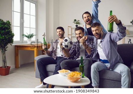 Group of excited men friends football fans feeling happy and celebrating favourite teams goal drinking beer and eating snacks during watching television match at home. Entertainment for male company Royalty-Free Stock Photo #1908349843