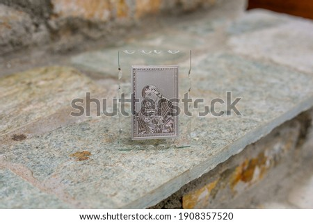 A closeup of a small picture of the Virgin Mary holding Jesus Christ in a frame on a rough surface
