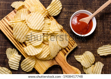Wavy, potato chips in a plate with ketchup on a wooden table. Top view of snacks. Stock photo potato chips with empty space.