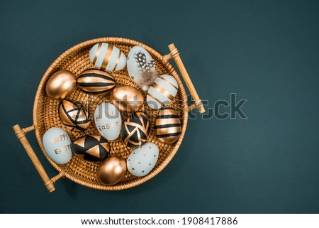 Gold, black, white eggs on a trendy emerald background. Geometry. The minimal concept. Top view. An Easter card with a copy of the place for the text.