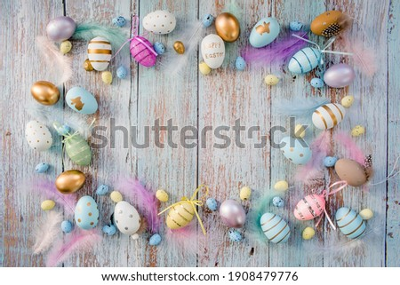 Banner. Easter frame with eggs and feathers on a blue wooden background. The minimal concept. Top view. Card with a copy of the place for the text. Royalty-Free Stock Photo #1908479776