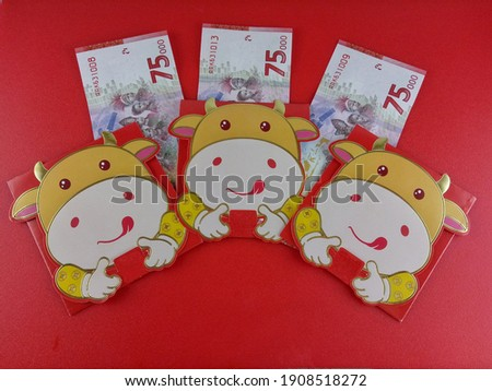 Celebrating Chinese New Year The Year of The Ox. 3 Angpao or Red Packets with Cute Ox Cartoon Design and Three Special Edition 75 Thousand Indonesian Money, Celebrating 75 Years of Independence