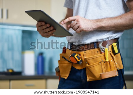 Cropped shot of young repairman wearing a tool belt with various tools using digital tablet while standing indoors Royalty-Free Stock Photo #1908547141