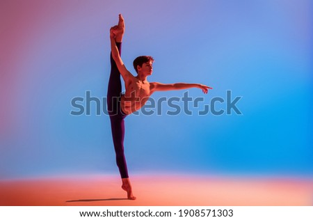 teenage ballet dancer dances barefoot under a colored light. Royalty-Free Stock Photo #1908571303