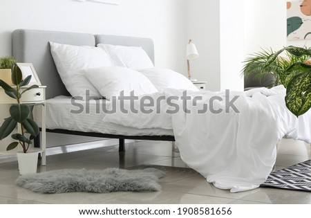 Big comfortable bed with clean linen in room Royalty-Free Stock Photo #1908581656