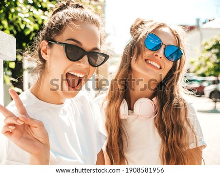 Portrait of two young beautiful smiling hipster female in trendy summer white t-shirt clothes.Sexy carefree women posing on street background. Positive models having fun, hugging and going crazy Royalty-Free Stock Photo #1908581956