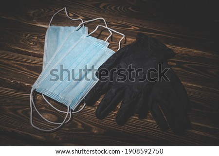 Medical masks and black medical rubber gloves on a wooden background. Covid-19 virus protection concept. Low key studio photo with vignetting.