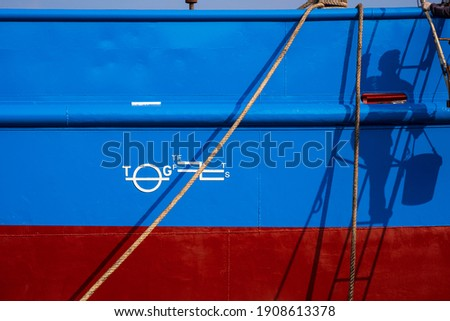 Sunlight and shadow of painter climbing ladder with white plimsoll mark on blue and red rust proof steel hull surface of fishing vessel with mooring rope in shipyard area