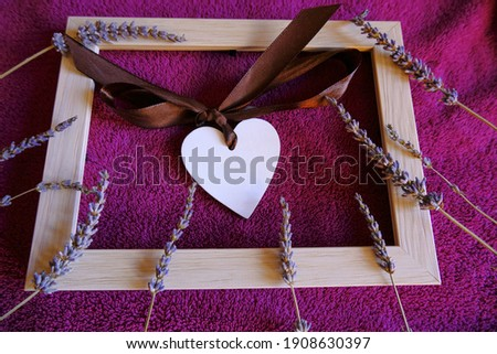 White wooden heart with silk bow across wooden picture frame with lavender on purple textile background close-up. Love concept, St. Valentine's day