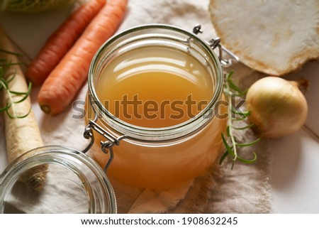 Homemade beef bone broth in a glass jar, with carrots, celery root and other fresh vegetables
