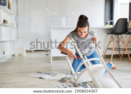 Woman as a handyman at home painting a chair or painting as upcycling Royalty-Free Stock Photo #1908654307