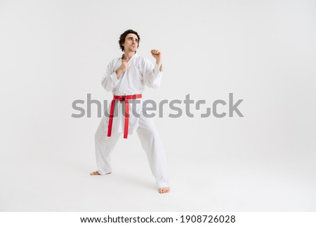Young caucasian sportsman dressed in kimono practice in karate isolated over white background Royalty-Free Stock Photo #1908726028