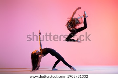 two ballet girls with long loose hair in black tight-fitting suits dancing on a red background Royalty-Free Stock Photo #1908731332
