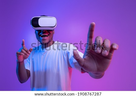 Augmented reality world. Excited black millennial guy in vr glasses, touching virtual button while playing video game in goggles, standing in neon light over purple background, copy space Royalty-Free Stock Photo #1908767287