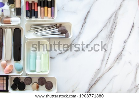 Top view of female visagiste is neatly placing cosmetic and vanity items in MUJI's PP makeup storage boxes with various sizes on white marble dressing table. Decluttering and organization concept. Royalty-Free Stock Photo #1908771880