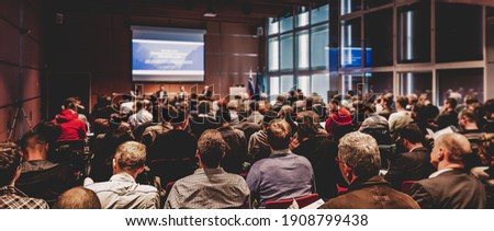 Business and entrepreneurship symposium. Speaker giving a talk at business meeting. Audience in conference hall. Rear view of unrecognized participant in audience. Royalty-Free Stock Photo #1908799438
