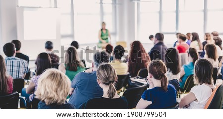 Business and entrepreneurship symposium. Female speaker giving a talk at business meeting. Audience in conference hall. Rear view of unrecognized participant in audience. Royalty-Free Stock Photo #1908799504