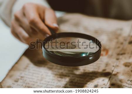 Historian scientist reading antique book with magnifying glass. Translation of religious literature. Manuscript with ancient writings. Treasures of the past. Museum piece Royalty-Free Stock Photo #1908824245