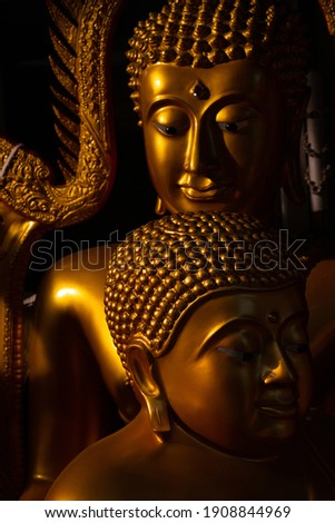 Face of Golden Buddha statue illuminated isolated on black background. Close up of two face Buddha statue with light and shadow in peace. The Buddha statue and Buddhist saint. Head of the Buddha image