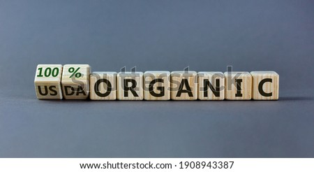 100 percent organic symbol. Fliped wooden cubes and changed words non-organic to 100 percent organic. Beautiful grey background, copy space. Business, healthy lifestyle 100 percent organic concept. Royalty-Free Stock Photo #1908943387