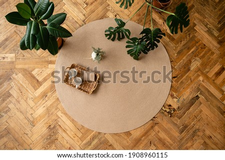 Jute Twine round Mat rug eco style with green plant. Knitted at home decoration concept. round brown natural linen bed mat near green potted plants Royalty-Free Stock Photo #1908960115