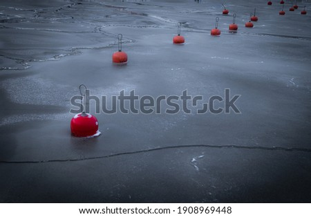 Red buoys frozen in ice of empty yacht marine waters.   Royalty-Free Stock Photo #1908969448