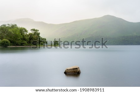 Sunrise on Derwent Water in the Lake District National Park, Cumbria England.  The sun is shining on the trees in the midground and the moring mist is lighting out Cat Bells in the background. Royalty-Free Stock Photo #1908983911