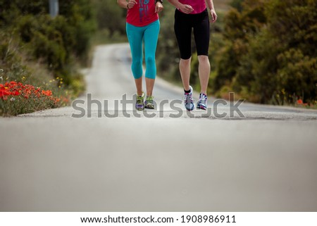 Detail photo of two woman running on a street in the landscape focus on their feet