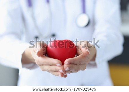 Female doctor holding red toy heart in her hands closeup. Internal organ transplant concept Royalty-Free Stock Photo #1909023475