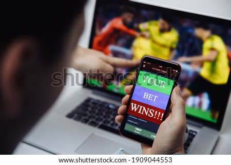 Man watching football online broadcast on his laptop and celebrate victory in betting at bookmaker's website. Betting and gambling concept Royalty-Free Stock Photo #1909044553