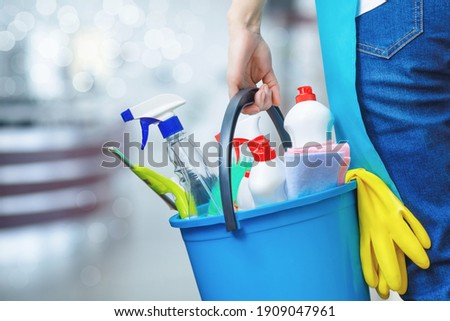 Cleaning lady holding a bucket of cleaning products in her hands on a blurred background. Royalty-Free Stock Photo #1909047961