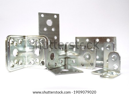 On a white background, a close-up of fastening corners for fastening various building materials. Royalty-Free Stock Photo #1909079020