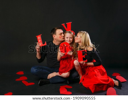 The family keeps the word LOVE love is a symbol of happiness , on the floor of hearts beautiful wedding. the honeymoon form. event forever, joy in a red dress girl, barefoot