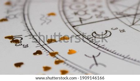 Detail of printed natal chart with astrology moon and heart shaped golden sequins Royalty-Free Stock Photo #1909146166
