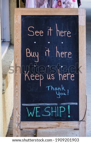 Handwritten sign on portable chalkboard in front of small retail store during pandemic and economic downturn, for themes of consumerism, local enterprise and tourism