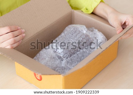 Closeup hand of woman opening parcel box with check product at home, female unpack with knife, delivery and shipping, shipment and express for shop, online shopping store and service concept.
