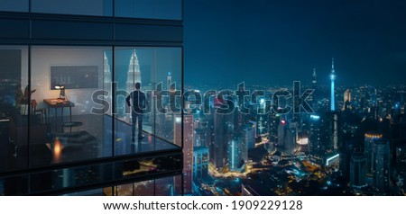 Young business man standing in the 3d rendering office watching the modern city night view, view from the outside. Business ambition concept. Royalty-Free Stock Photo #1909229128