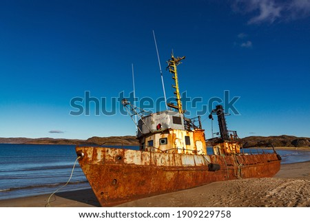 A wrecked ship on a sandy beach at low tide in the Teriberskaya Bay. Far North, Barents Sea in Russia. Royalty-Free Stock Photo #1909229758