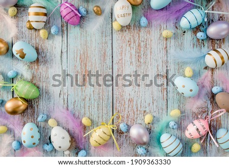 Banner. Easter frame with eggs and feathers on a blue wooden background. The minimal concept. Top view. Card with a copy of the place for the text. Royalty-Free Stock Photo #1909363330